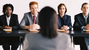 a young graphic designer interviews in front of a panel of interviewers. The panel consists in two women and two men. We can see only the back of the candidate