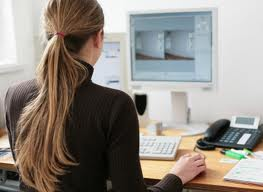 Young designer working at the computer. We can see a telephone, a screen, a keyboard, and many papers on her table. The picture illustrates a typical setting for an entry level designer